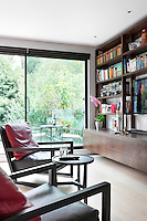 A modern living room with a sliding glass door, which leads to the garden. The room is furnished with a built in floor to ceiling shelving unit and two armchairs face a wall mounted television