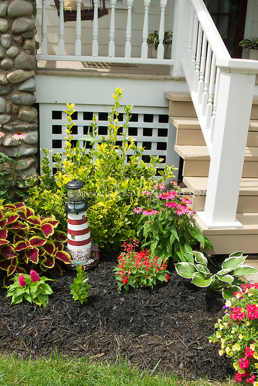 Lighthouse ornament in mulched front garden with annuals and shrubs and perennials next to porch steps of house