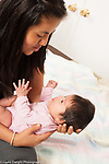 7 week old newborn baby girl held by mother interaction, talking to her