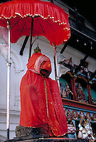 Dressed Buddha statue in Nepal. Statues of Buddha are often well tended, given red (happy) cloth to wear, protected by parasols and are given offerings of flowers, water and food. Katmandu, Nepal.