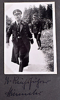 BNPS.co.uk (01202 558833)<br /> Pic: C&amp;TAuctions/BNPS<br /> <br /> Included in its pages is a candid shot of SS Chief Himmler in playful mood.<br /> <br /> A photo album containing never-before-seen candid snaps of Adolf Hitler that was found in Eva Braun's bedroom drawer in the Fuhrer's Bunker has sold for more than &pound;41,000.<br /> <br /> The remarkable images show the Nazi dictator and his henchmen in rare lighter moments of the Second World War.<br /> <br /> The album, which was unearthed after 72 years, sparked fervent interest and attracted a phone bid of more than double its estimate of &pound;18,000.<br /> <br /> The hammer price was &pound;34,000, with extra fees pushing the final total to &pound;41,140.<br /> <br /> There is one snap of a grinning Hitler in a 'Chaplinesque' pose and offering a playful salute to the person taking the photo outside his Berghof headquarters. Two more show him smiling in front of a crowd of children saluting him.