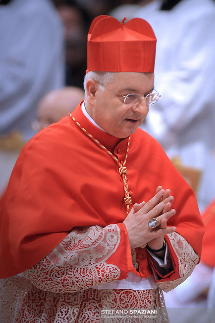 Italian newly appointed Cardinal Mauro Piacenza  (C) gets his biretta, the square red hat symbolising the blood of the martyrs, from Pope Benedict XVI (L) on November 20, 2010 during a consistory at St Peter's basilica at The Vatican. 24 Roman Catholic prelates join today the Vatican's College of Cardinals, the elite body that advises the pontiff and elects his successor upon his death