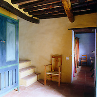 In this corridor an antique cupboard has been painted a deep turquoise in contrast to the pale yellow walls