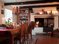 Candles illuminate the mantelpiece above the kitchen hearth at Helgagaarden farm
