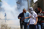 Palestinian protesters take cover from a tear gas canister fired by Israeli forces during clashes following a weekly demonstration against the expropriation of Palestinian land by Israel in the village of Kfar Qaddum, near the West Bank city of Nablus on September 7, 2018. Photo by Shadi Jarar'ah