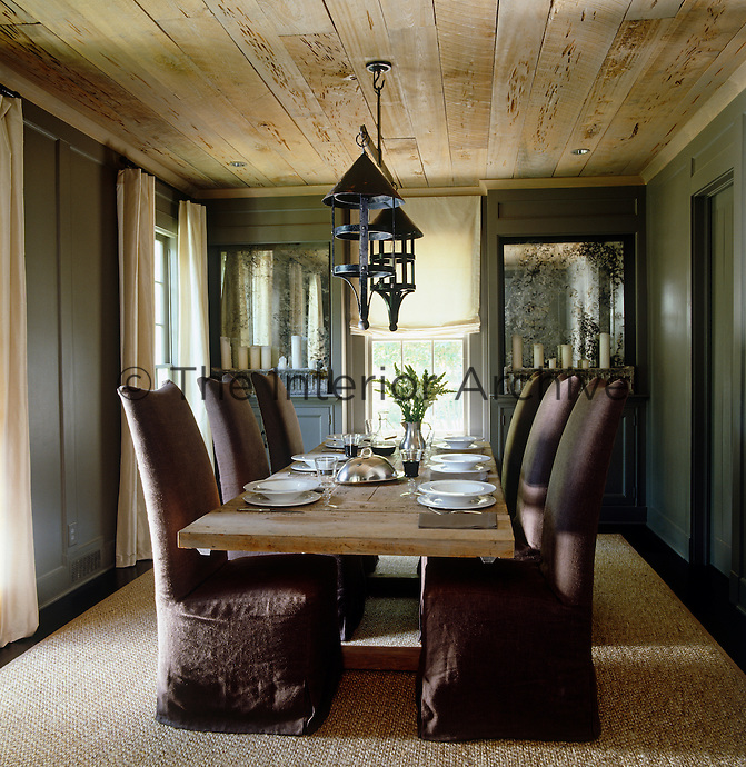 The chocolate brown loose covers on the chairs coupled with the timeworn table create an understated European elegance in the dining room