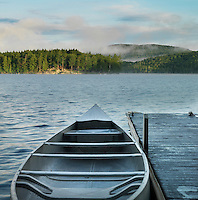 Morning mist evaporates slowly over a lake and forest in the Adirondack mountains