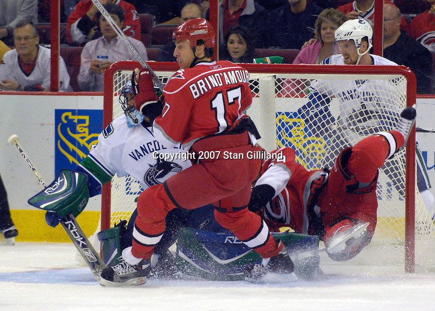 Carolina Hurricanes Chad LaRose, right, falls into the Vancouver Canucks' goalie Roberto Luongo as Rod BrindA'mour skates through during their game Monday, Oct. 22, 2007 in Raleigh, NC. The Hurricanes won 3-1.