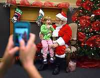STAFF PHOTO BEN GOFF  @NWABenGoff -- 12/13/14 Charlotte Bearden, 3, takes a seat on Santa's lap while a volunteer snaps a photo during Explore and Discover Preschool's 22nd annual Breakfast with Santa event at First United Methodist Church in Bentonville on Saturday Dec. 13, 2014. Children could get their picture taken with Santa Claus and pick up a print after breakfast with their family during the fundraiser supporting the church's Explore and Discover Preschool.