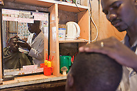Octopizzo at the barbershop in Kibera where he gets his trademark 8 shaved on his scalp.