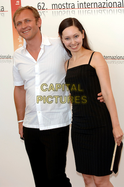 "ANDRZEI CHYRA & MARIA BEKKER.photocall for ""Persona Non Grata"",.62nd International Film Festival,.Venice, 4th September 2005.half length La Biennale white shirt black trousers pin stripe dress purse clutch bag hand waist.Ref: PL.www.capitalpictures.com.sales@capitalpictures.com.©Capital Pictures."