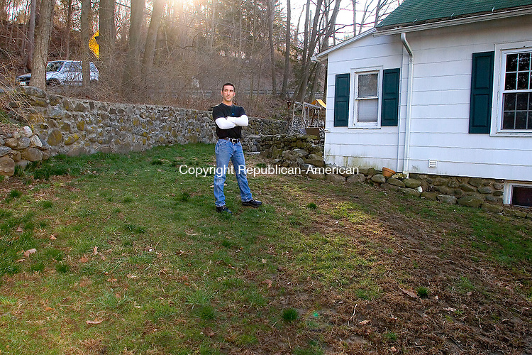 MIDDLEBURY, CT - 21 APRIL 2007 - 042107JW01.jpg -- Ed Cavallaro poses for a phot outside his home on Glenwood Avenue Saturday morning. Cavallaro is suing the town of Middlebury citing that the sewer and water line work that the town did to the nearby Colonial Avenue has caused flooding through the retaining wall into his yard and house.  Jonathan Wilcox Republican-American