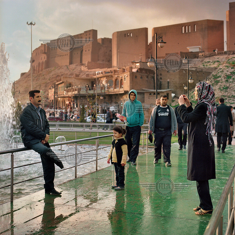 A man poses while his wife takes a picture on a bridge leading up to the bottom of the mount that houses the ancient Citadel of Arbil. The Citadel is an inhabited mound in the centre of the modern Iraqi city of Erbil, which is said to be one of the oldest, continually inhabited places in the world. Earliest traces of habitation on the mound date back to the 5th millennium BC, possibly earlier. The city of Erbil, the fourth biggest in Iraq, is today the capital of Iraqi Kurdistan. .Since 2007 the High Commission for Erbil Citadel Revitalisation (HCECR) has been in charge of the Citadel complex and is carrying out major reconstruction efforts since moving out all remaining residents. It is hoped that 50 families will move back into the Citadel once renovation work and archeological digs have been completed. .