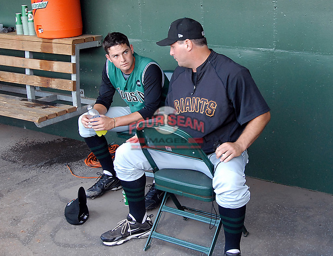 Pitching coach Steve Kline talks with starting pitcher Chris Heston (23) of the Augusta GreenJackets in a corner of the dugout after after a difficult inning of a game against the Greenville Drive on May 20, 2010, at Fluor Field at the West End in Greenville, S.C.