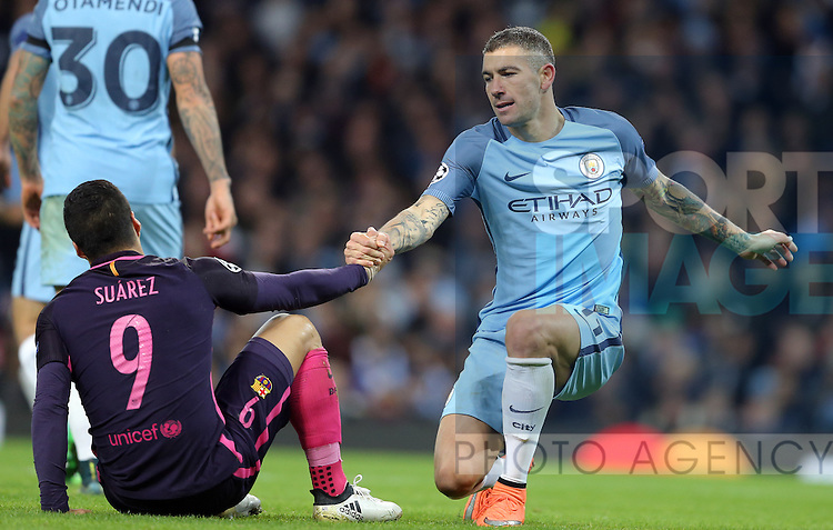 Luis Suarez of Barcelona is helped up by Aleksander Kolarov of Manchester City during the Champions League Group C match at the Etihad Stadium, Manchester. Picture date: November 1st, 2016. Pic Simon Bellis/Sportimage