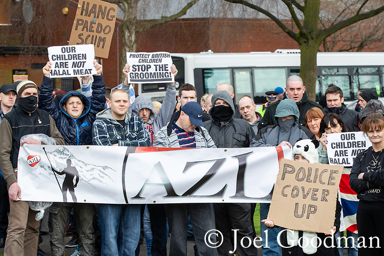 "© Joel Goodman - 07973 332324 . 03/03/2012 . Heywood , UK . Protesters hold an "" Anti Zionist League "" banner and placards reading "" Hang paedo scum "", "" Our children are not halal meat "" , "" Police cover up "" and "" Protect british children stop the grooming "" . The National Front hold a rally in protest against an alleged paedophile ring that had been operating in the area . There is currently (3rd March 2012) a case being tried at Liverpool Crown Court in relation to the allegations . Last Thursday (23rd February 2012) a protest organised in the town in relation to the same story resulted in Asian business being attacked by an angry mob . Photo credit : Joel Goodman"