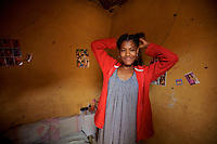 Asmar Maharate, 18, sex worker from Goldon, ties her hair moments after a colleague of hers added new extensions to it in her private room in Babile, Ethiopia on Monday August 14 2006..tens of young girls work in small bars in the boarder town of Babile, where the rat of HIV infections is among the highest in the country. they seel their bodies for less than 2 USD. None of these girls test for HIV and frequently are frequently forced into unprotected sex..Ethiopia is one of the countries most affected by HIV/AIDS. Of its population of 77 million, three million are HIV-positive, according to government statistics. Every day sees 1,000 new infections. A million children under 14 have lost one or both parents to AIDS, and 200,000 children are living with AIDS. That makes Ethiopia the country with the most HIV-positive children.