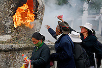 Tibetan Buddhist pilgrims offer water and barley flour at an incense burner on the Barkhor circuit around the Jokhang Temple during Saga Dawa festival, Lhasa, Tibet.