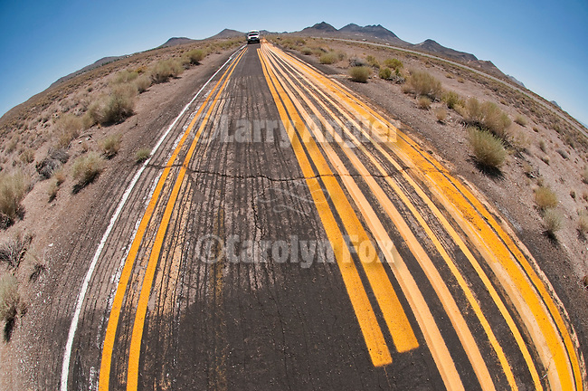 Follow the yellow brick road. Yellow painted barrier striping used to test highway spray rig or to practice on abandoned paved roadway in central Nevada..