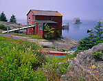 Lunenburg County, Nova Scotia, Canada: Red and grey boat houses at Blue Rocks village on foggy Lunenburg Bay