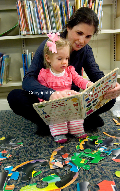 SOUTHBURY CT. 31 February 2014-020414SV03-Molly McEvoy, 1, and her mom, Ashley McEvoy of Southbury read a book in the children&rsquo;s section of the library in Southbury Tuesday. They were there for the Babies &amp; Books program. The program was canceled due to Region 15 school delay, but the moms and kids made the best of it playing and reading.<br /> Steven Valenti Republican-American