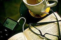 an MP3 player, cup of tea on a vinyl record and an open book with a pair of eyeglasses on it.