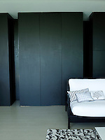 Black-painted built-in cupboards line the back wall of the open-plan living/dining area