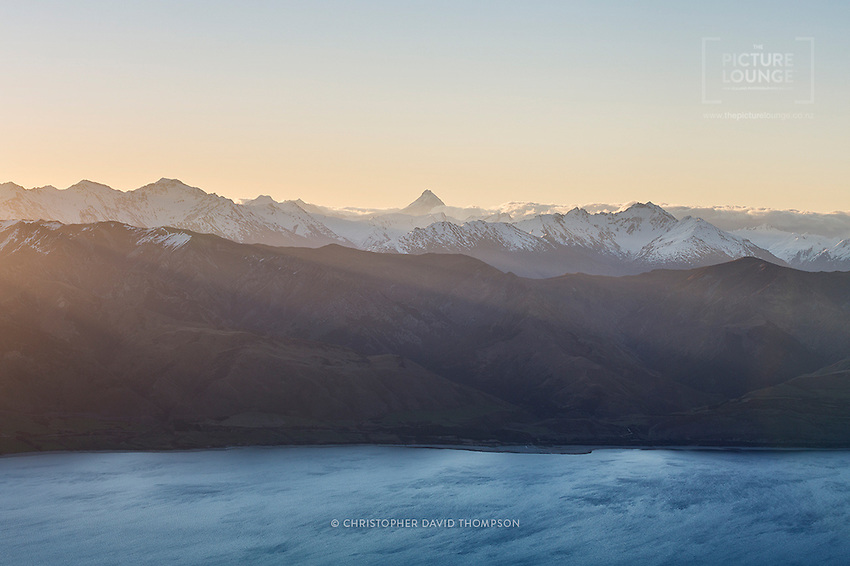 Does Central Otago get more beautiful than this? A stunning spring evening shot taken by NZ landscape photographer Christopher David Thompson whilst hiking the Breast Hill Track. Beams of sunlight glitter upon the surface of Lake Hawea far below, with the pyramidal peak of Mt Aspiring dominating the skyline in the distance.