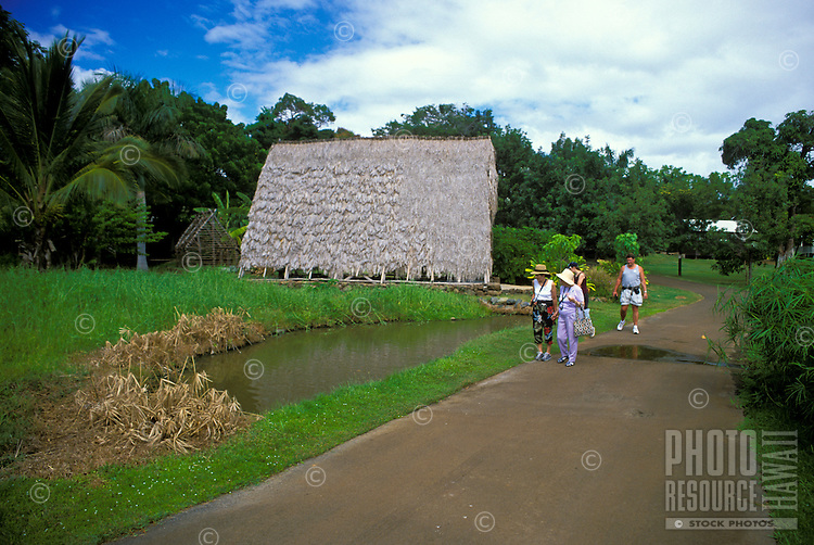Tourists get a taste of the early days of life in Hawaii as they stroll thru Hawaii's Plantation village.