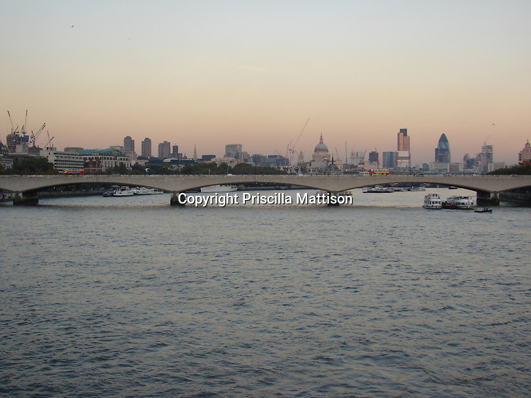 London, England - November 6, 2006:  Waterloo Bridge spans the Thames at sunset, with the London cityscape spread out in the background.