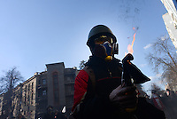 A protester ignites a petrol bombs to be next launched towards the riot police. Kiev, Ukraine
