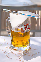 A big glass of cold beer Pivo, condensation on the glass, on a white table cloth, pine needles on the table, the glass covered with a napkin and a knife to protect from getting needles in the beer Hotel and restaurant Kompas. Uvala Sumartin bay between Babin Kuk and Lapad peninsulas. Dubrovnik, new city. Dalmatian Coast, Croatia, Europe.