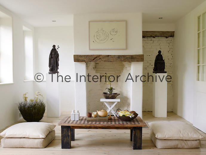 An additional small living room is furnished with floor cushions and a low table - ideal for drinking tea and meditation - and carved figures are displayed on plinths  in the alcoves next to the rustic fireplace
