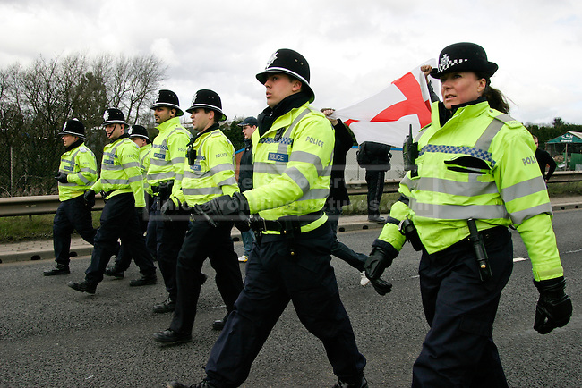 Police escort a group of demonstrators to the EDL holding area on a duel carriageway outside Dudley town centre.