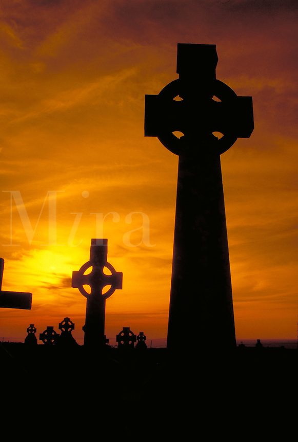Two Celtic Crosses are silhouetted against golden sunset light in an Ancient Cemetery. These stone sculptures symbolize the Christian heritage of Ireland. County Clare, Ireland.
