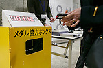 A woman donates her old mobile phone to make medals for the 2020 Tokyo Olympic and Paralympic Games at Tokyo Metropolitan Government Building on February 21, 2017, Tokyo, Japan. Tokyo Government has asked for people to donate their old electronic gadgets (including smart phones, mobile phones and tablets) with the aim of collecting and recycling eight tonnes of gold, silver and bronze to make the 5,000 medals needed for the 2020 Tokyo Olympic and Paralympic Games. The recycling campaign started on Thursday, February 16. (Photo by Rodrigo Reyes Marin/AFLO)