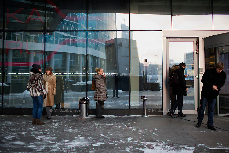 People smoke outside a building in Moscow City development area in Moscow, Russia.