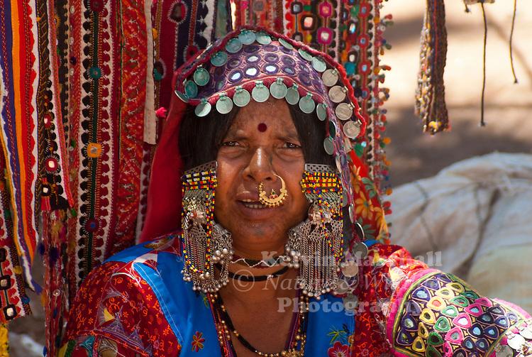 A portrait of a Rajasthani women wearing traditional clothing and jewellery. Anjuna markets, Anjuna beach - Goa India.