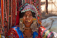 A portrait of a Rajasthani women wearing traditional clothing and jewellery. Anjuna markets, Anjuna beach - Goa India.