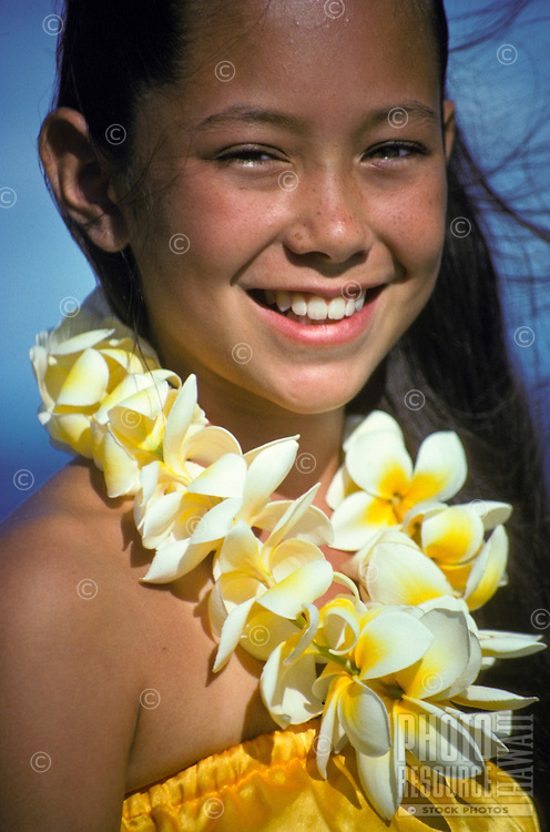 Young island girl, age 9-10, wearing a yellow plumeria lei and hula costume in Hawaii