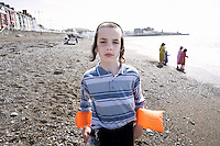 An Hasidic boy wears arm bands on the beach in Aberystwyth.