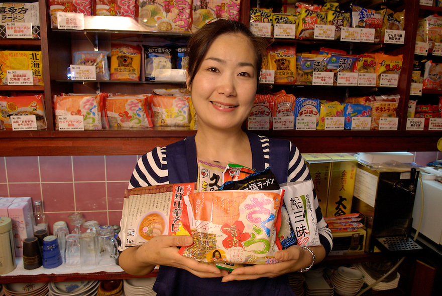 Staff member at Sakura instant ramen restaurant Chie Tanaka holds a selection of instant ramen. Some of 200 varieties of instant ramen are on the shelves. Owner Sakura Takenaka founded the restaurant 2 years ago and now has 10 franchises over Japan.