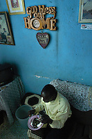 Dennis Serwanga has lunch in the home he shares with his sister and her family in Naguru Estates, Kampala, Uganda.   The Kampala City Council was planning to sell the land of the estates to developers and gave tennants of the low-income housing area six months to move out. Popular protests stopped the plan. (Rick D'Elia)<br />