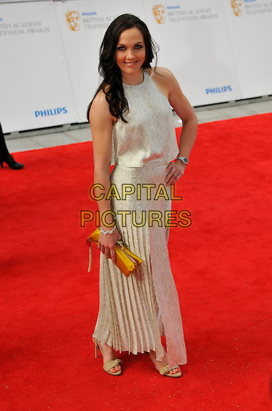 VICTORIA PENDLETON.Attending the Philips British Academy Television Awards, Grosvenor house Hotel, Park Lane, London, England, UK, May 22nd 2011..arrivals TV Baftas Bafta full length cream white print pleated skirt dress hand on hip clutch bag sleeveless  yellow .CAP/CAS.©Bob Cass/Capital Pictures.