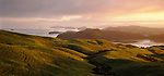 Sunrise over coastal Coromandel Peninsula. Farmland in foreground. New Zealand