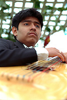 Musician age 19 playing guitar at Cinco de Mayo festival.  St Paul Minnesota USA