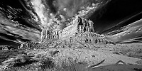 Infrared photo from the Valley of the Gods. The statuesque sentinels in the Valley of the Gods, as well as other area features, are all sculpted from Cedar Mesa sandstone dating to the Permian age, 250 million years old. The 1200 foot thick sandstone was cemented by calcium carbonate interspersed with lenses of red siltstone and was deposited in huge sand dunes near the shores of an ancient sea. Erosion by water, wind and ice over millions of years chiseled rock formations into the unique shapes we see today.