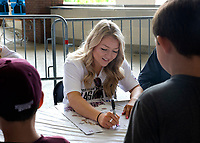 Women's basketball player Blair Schaefer signing a poster during the women's basketball autograph session in David Wade stadium.<br />  (photo by Lizzy Powers / &copy; Mississippi State University)