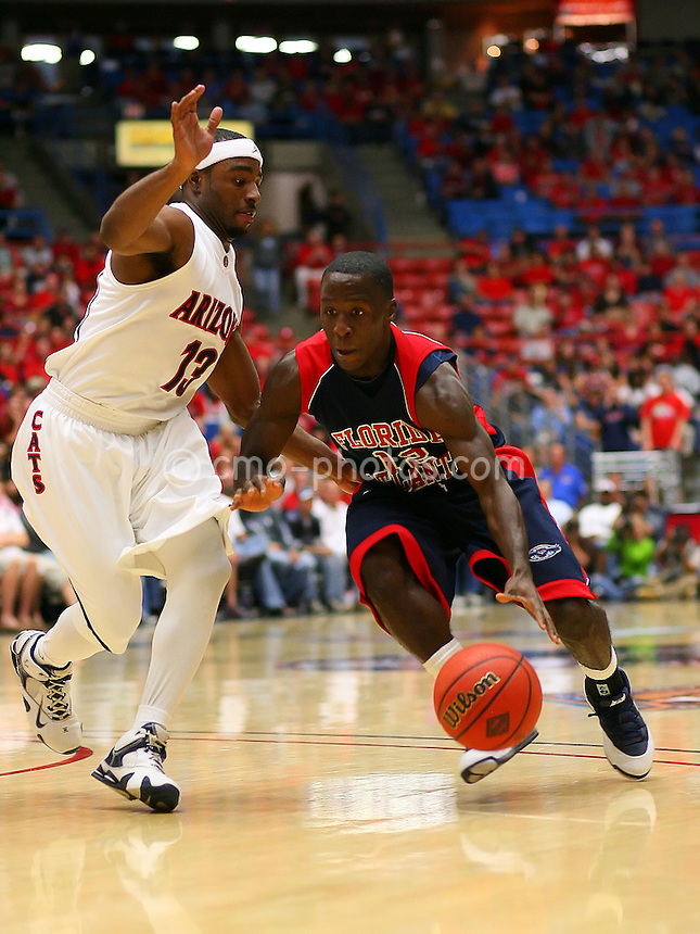 Nov 17, 2008; Tucson, AZ, USA; Florida Atlantic Owls guard Carderro Nwoji  (12) tries to dribble around Arizona Wildcats guard Nic Wise (13) in the first half of a NIT Season Tip-Off game at the McKale Center.  Arizona won the game 75-62.  Mandatory Credit: Chris Morrison-US PRESSWIRE