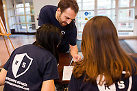 Claris Chang (from left), 25, Joseph Manganiello, 24, and Meredith Davis, 26, all Master in Public Policy grad students at Harvard, wait to register attendees before a session of Resistance School at Harvard University's John F. Kennedy School of Government, on Thurs., April 27, 2017.